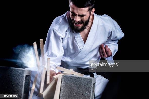 karateka breaking a wooden board with his hand - martial arts stock pictures, royalty-free photos & images