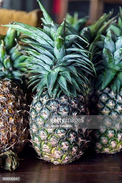 Fresh spiky pineapples resting on a shelf in a breakfast dining room.