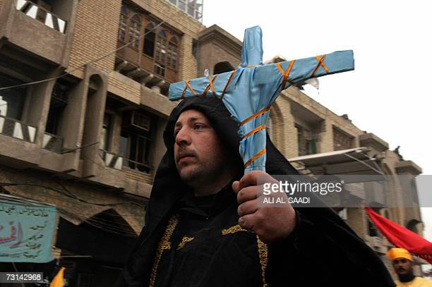 A Shiite pilgrim carries a cross as he plays the role of a Christian priest who sculpted the head of Prophet Mohammed's grandson Imam alHussein...