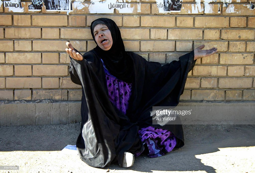 An Iraqi woman weeps beside the bodies ( : News Photo