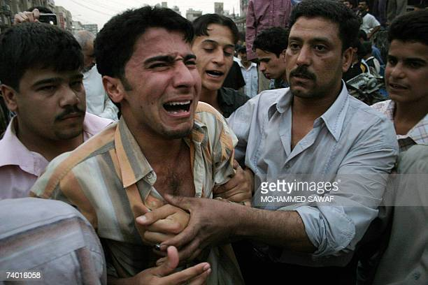 Iraqis try to comfort a weeping man at the site of a suicide car bomb in the holy city of Karbala central Iraq 28 April 2007 A suicide car bomb...