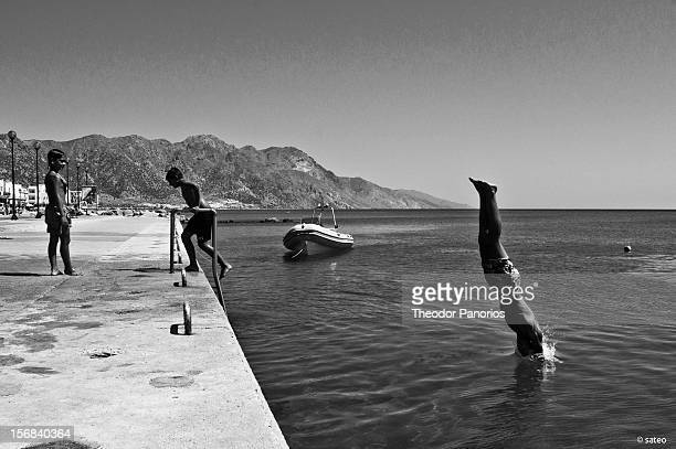 Kardamena harbour, Kos island, Greece. One young man dips into the sea, another exits.