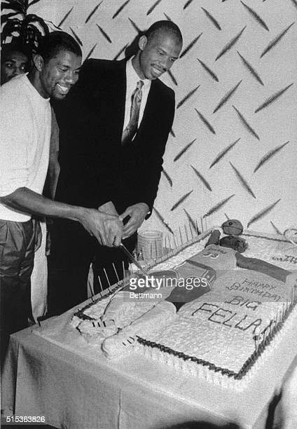 Kareem Abdul Jabbar gets a helping hand from Lakers' teammate Magic Johnson as AbdulJabbar cuts the cake to mark his 40th birthday at a party The...