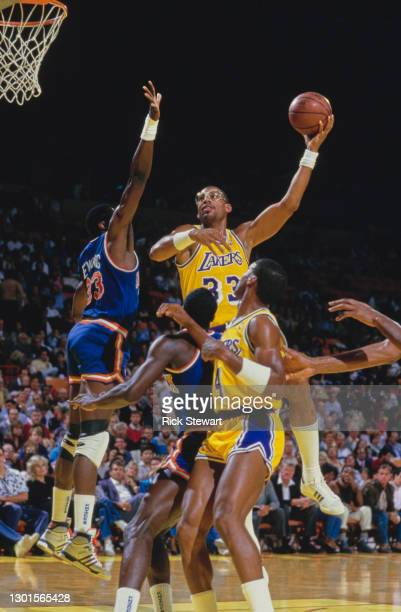 Kareem Abdul-Jabbar, Center for the Los Angeles Lakers jumps to make a lay up shot to the basket over Patrick Ewing of the New York Knicks during...