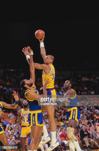 Kareem Abdul-Jabbar, Center for the Los Angeles Lakers jumps to make a single handed layup shot to the basket over Joe Barry Carroll, Center for the...