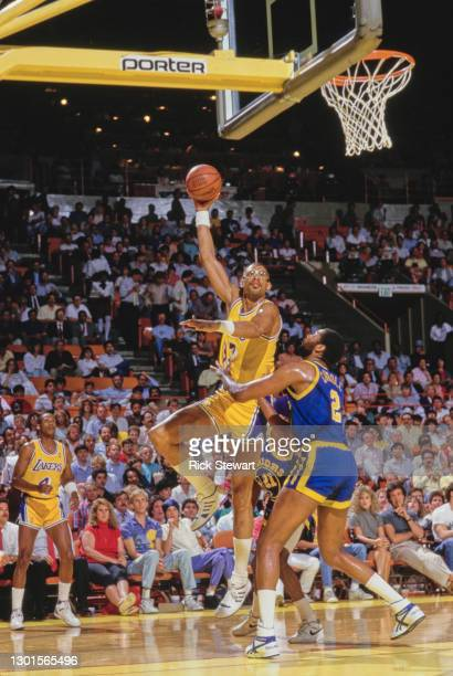 Kareem Abdul-Jabbar, Center for the Los Angeles Lakers jumps to make a single handed lay up shot to the basket over Joe Barry Carroll, Center for the...