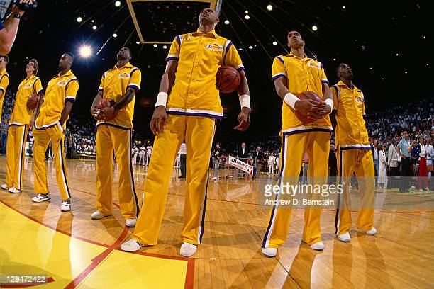 Kareem AbdulJabbar Mychal Thompson and Magic Johnson of the Los Angeles Lakers stand during the national anthem prior to Game Two of the 1988 NBA...