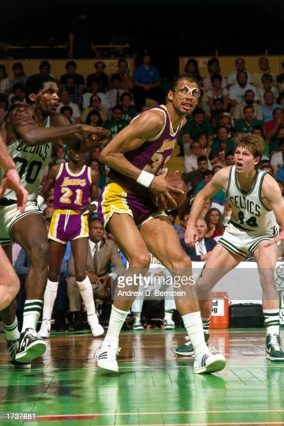 Kareem Abdul-Jabbar of the Los Angeles Lakers drives to the basket as Danny Ainge and Robert Parish of the Boston Celtics defend during the 1984 NBA...