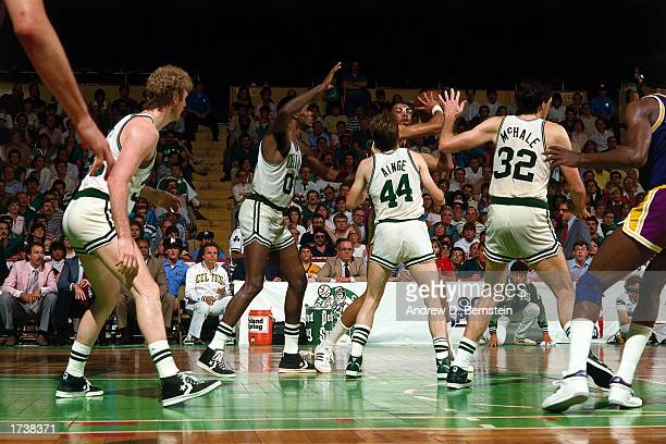 Kareem AbdulJabbar of the Los Angeles Lakers looks to make a pass while being defended by Larry Bird Robert Parish Danny Ainge and Kevin McHale of...