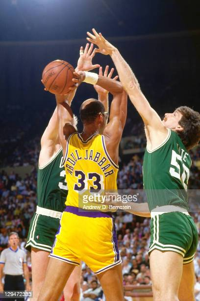 Kareem AbdulJabbar of the Los Angeles Lakers passes against Tom Kite and Larry Bird of the Boston Celtics during Game One of the 1987 NBA Finals on...