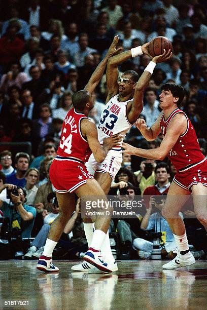 Kareem AbdulJabbar of the Western Conference AllStars is surrounded by Eastern Conference AllStars Hakeem Olajuwon and Bill Laimbeer during the 1987...