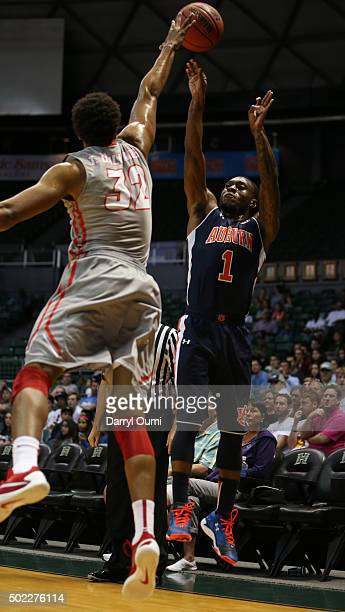 Kareem Canty of the Auburn Tigers shoots over Tim Williams of the New Mexico Lobos at the Stan Sheriff Center during the Diamond Head Classic on...