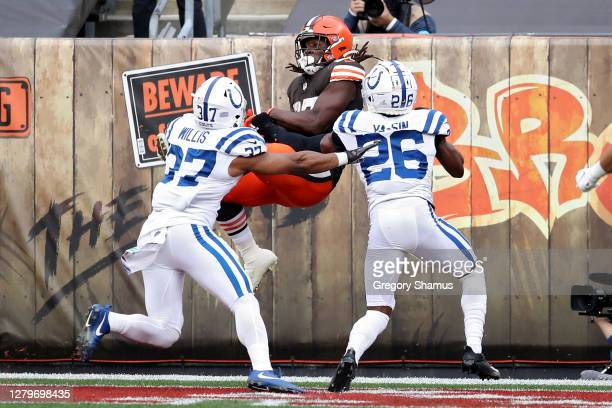 Kareem Hunt of the Cleveland Browns catches a touchdown pass while being guarded by Khari Willis and Rock Ya-Sin of the Indianapolis Colts in the...