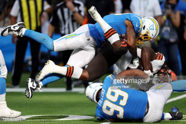 Kareem Hunt of the Cleveland Browns is hit by Derwin James and Jerry Tillery of the Los Angeles Chargers during the fourth quarter at SoFi Stadium on...