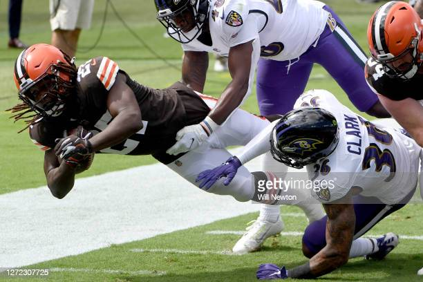 Kareem Hunt of the Cleveland Browns is tackled by Patrick Queen and Chuck Clark of the Baltimore Ravens during the first half at M&T Bank Stadium on...