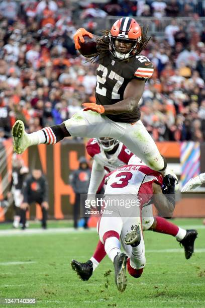 Kareem Hunt of the Cleveland Browns jumps over Budda Baker of the Arizona Cardinals during the fourth quarter at FirstEnergy Stadium on October 17,...