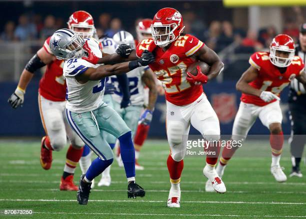 Kareem Hunt of the Kansas City Chiefs holds off Byron Jones of the Dallas Cowboys on a carry in the second half of a football game at ATT Stadium on...