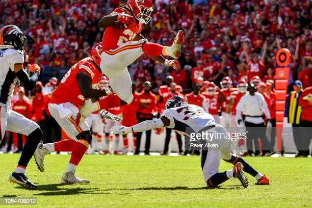 Kareem Hunt of the Kansas City Chiefs hurdles over Will Parks of the Denver Broncos on his way to an impressive touchdown run during the third...