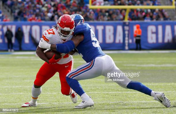Kareem Hunt of the Kansas City Chiefs in action against Jonathan Casillas of the New York Giants on November 19 2017 at MetLife Stadium in East...