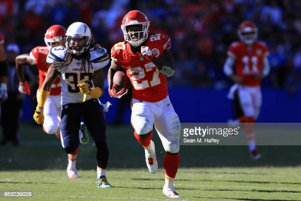 Kareem Hunt of the Kansas City Chiefs runs past Tre Boston of the Los Angeles Chargers for a touchdown during the second half of a game at StubHub...