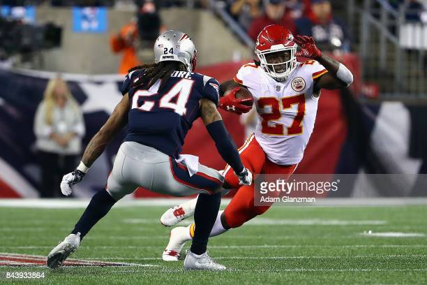 Kareem Hunt of the Kansas City Chiefs runs with the ball against Stephon Gilmore of the New England Patriots during the second half at Gillette...