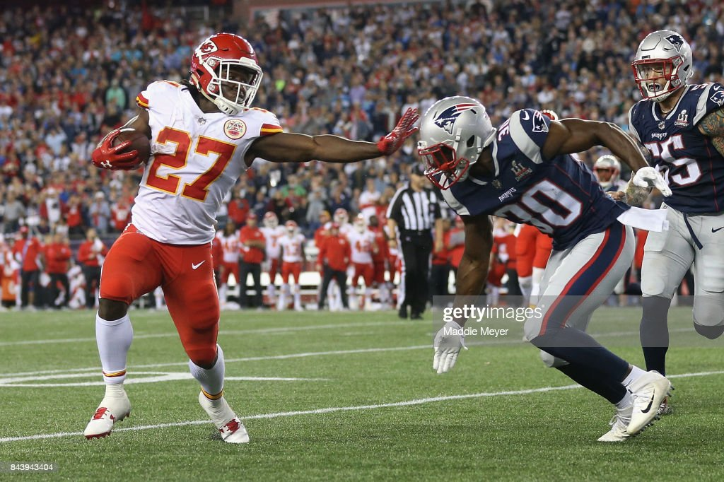 Kareem Hunt #27 of the Kansas City Chiefs stiff arms Duron Harmon #30 of the New England Patriots as he runs for a 4-yard rushing touchdown during the fourth quarter against the New England Patriots at Gillette Stadium on September 7, 2017 in Foxboro, Massachusetts.
