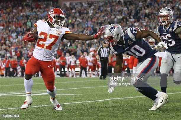 Kareem Hunt of the Kansas City Chiefs stiff arms Duron Harmon of the New England Patriots as he runs for a 4yard rushing touchdown during the fourth...