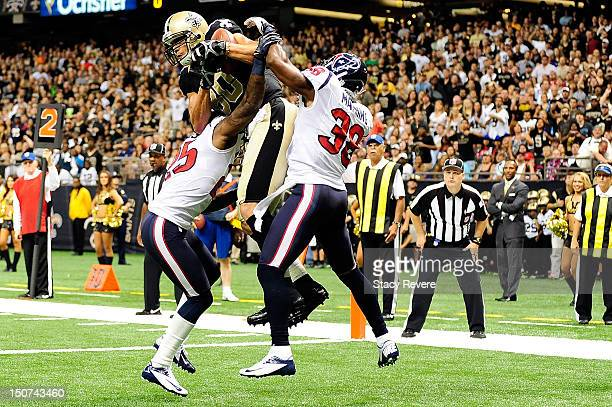 Kareem Jackson and Danieal Manning of the Houston Texans defend as Jimmy Graham of the New Orleans Saints catches a touchdown pass during a preseason...
