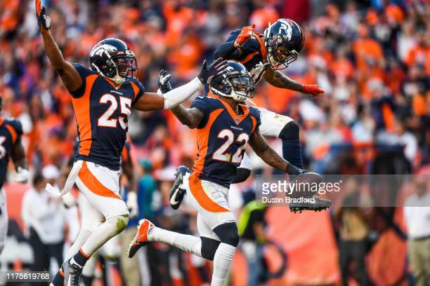 Kareem Jackson of the Denver Broncos celebrates with teammates Chris Harris and Justin Simmons after an interception in the fourth quarter against...