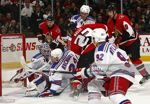 Karel Rachunek and Henrik Lundqvist of the New York Rangers try to control a loose puck with Chris Kelly of the Ottawa Senators trying to fight his...