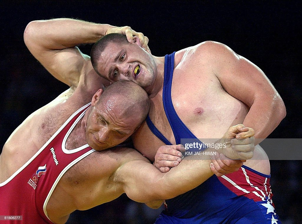 Kareline Alexandre of Russia (RED) attempts to power Rulon Gardner of the USA (BLUE) in the final of the men's 130kg Greco-Roman wrestling competition at the XXVII Olympic Summer Games 27 September 2000 in Sydney. American grizzly Gardner stopped giant Russian bear Karelin joining the ranks of Olympic immortals, shattering the defending champion's dreams of a fourth straight gold medal in a stunning upset. AFP PHOTO/KIM Jae-Hwan