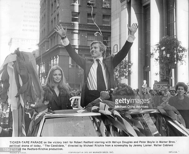 Karen Carlson sit in car and Robert Redford stands with hands raised in a scene from the film 'The Candidate' 1972