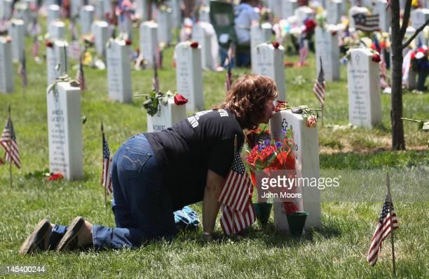 Karen Clarkson kisses her slain son's grave at the National Cemetery on Memorial Day May 28 2012 in Arlington Virginia Her son Sgt Joel Clarkson was...
