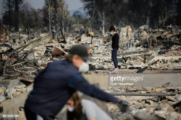 Karen Curzon looks at the destruction caused by the Tubbs Fire as her husband Ed and daughter Margaret use sifting trays donated by the Boy Scouts of...