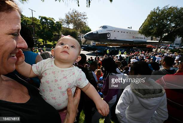 Karen Detrou holds her 7monthold baby Ella as the Space Shuttle Endeavour is moved to the California Science Center on October 13 2012 in Inglewood...