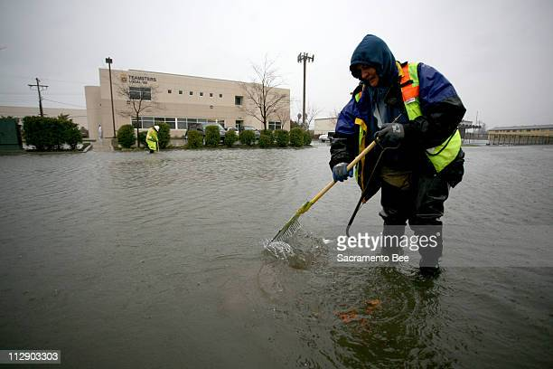 Karen Estep with the Department of Water Resources Stormwater Utility division uses a rake to unplug a storm drain in Sacramento California Friday...