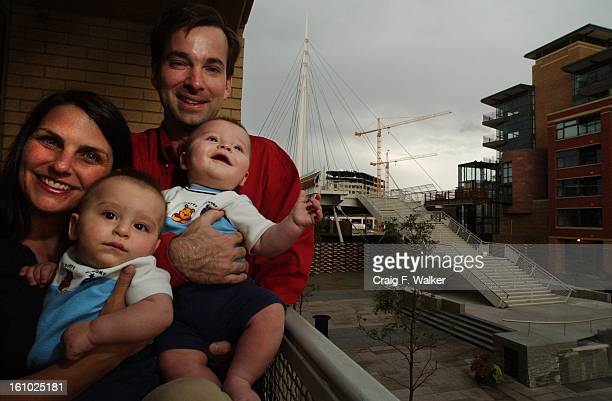 Karen Fischer holds onto twin Jake while her husband Darren Doyle comforts Seth during a portrait session on the balcony at Park Place Lofts in the...