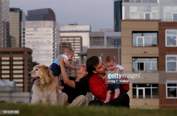Karen Fischer holds onto twin Jake while her husband Darren Doyle comforts Seth during a portrait session in the Park across the street from their...