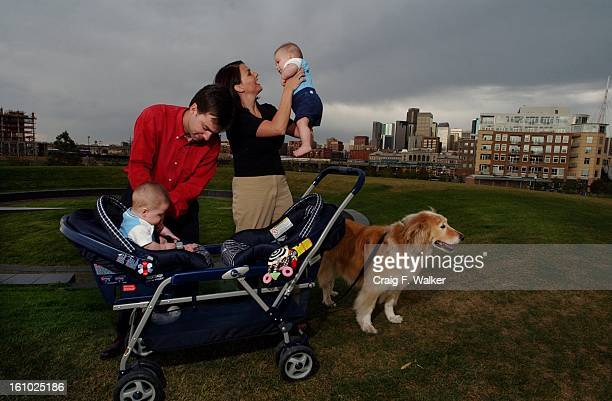 Karen Fischer holds onto twin Jake while her husband Darren Doyle secures Seth into a stroller while visiting the park across the street from their...