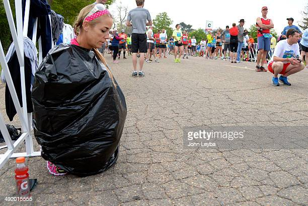 Karen Flynn of San Diego keeps warm in a trash bag before the start of the 1/2 marathon at the 9th annual Colfax Marathon May 18 2014 The 262 mile...
