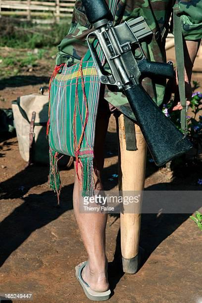 Karen guerrilla who has lost a leg on a landmine walks with his gun