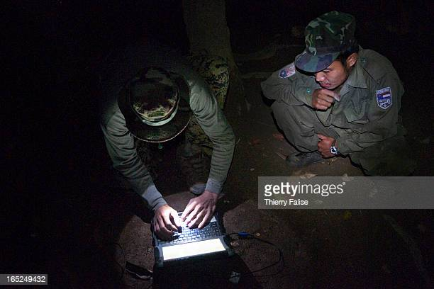 Karen guerrilla working as a security officer for a Free Burma Rangers relief team looks at a group's member typing a message on a portable computer