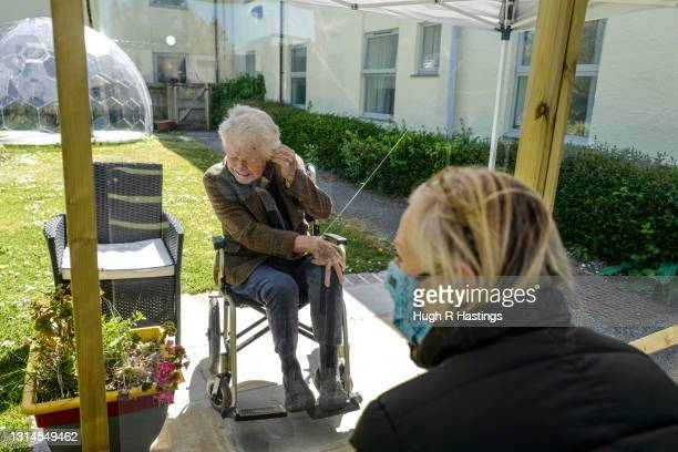 Karen Hastings visits her stepfather Gordon , who suffers from dementia, under a temporary open-air shelter with a clear screen between them, at the...