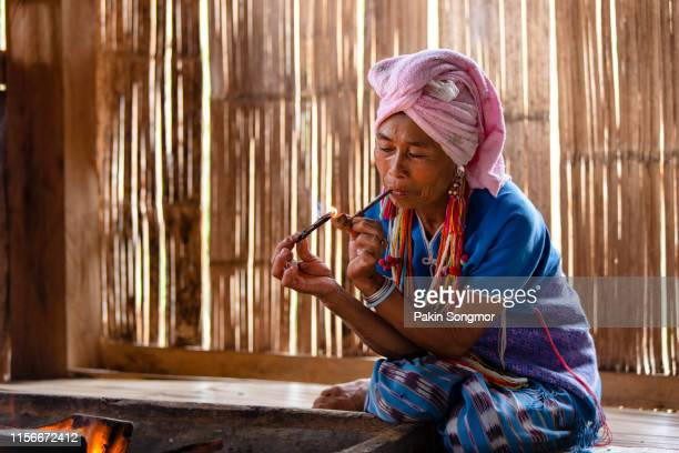 karen hill tribe is smoking tobacco pipe with traditional clothes in local village at hill area in chiang mai - ミャオ族 ストックフォトと画像