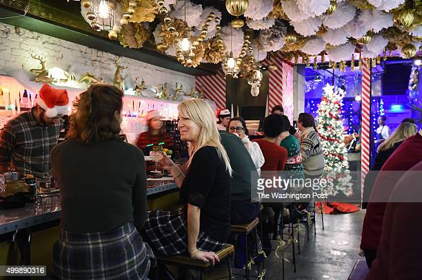 Karen Kaplan left and Tammy Merritt left center spend time at the holiday themed bar Miracle on Seventh Street on Tuesday December 01 2015 in...