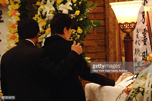 Karen Lao touches April Lao's face as she and husband Kam say their final good-byes to their daughter at her coffin prior to a traditional Buddhist...