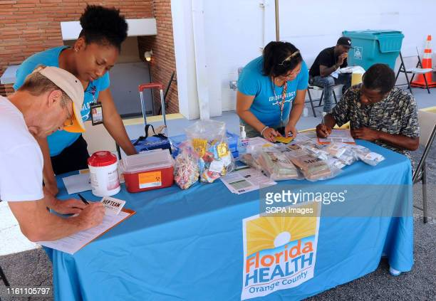 Karen McKenzie and Alvina Chu of the Orange County Florida Health Department register attendees to receive the hepatitis A vaccine at a vaccination...