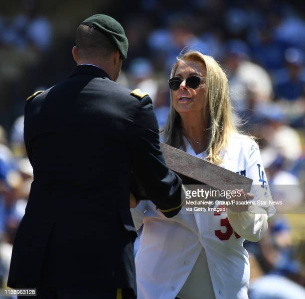 Karen Newcombe excepts a flag that was flown over the state capitol in honor of her late husband Don Newcombe prior to a MLB baseball game between...