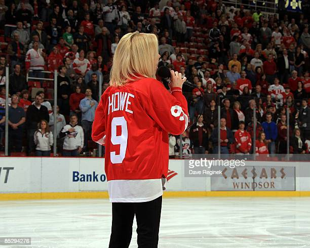 Karen Newman sings the national anthem wearing a Gordie Howe jersey in honor of his wife Colleen who passed away the day before a NHL game against...