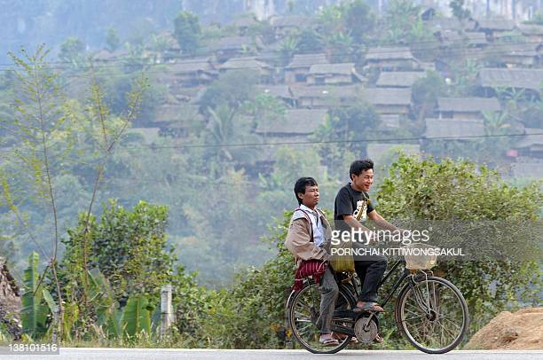 Karen refugees ride bicycle past temporary shelters at Mae La refugee camp in Mae Sot near the ThaiMyanmar border on January 29 2012 More than 140000...